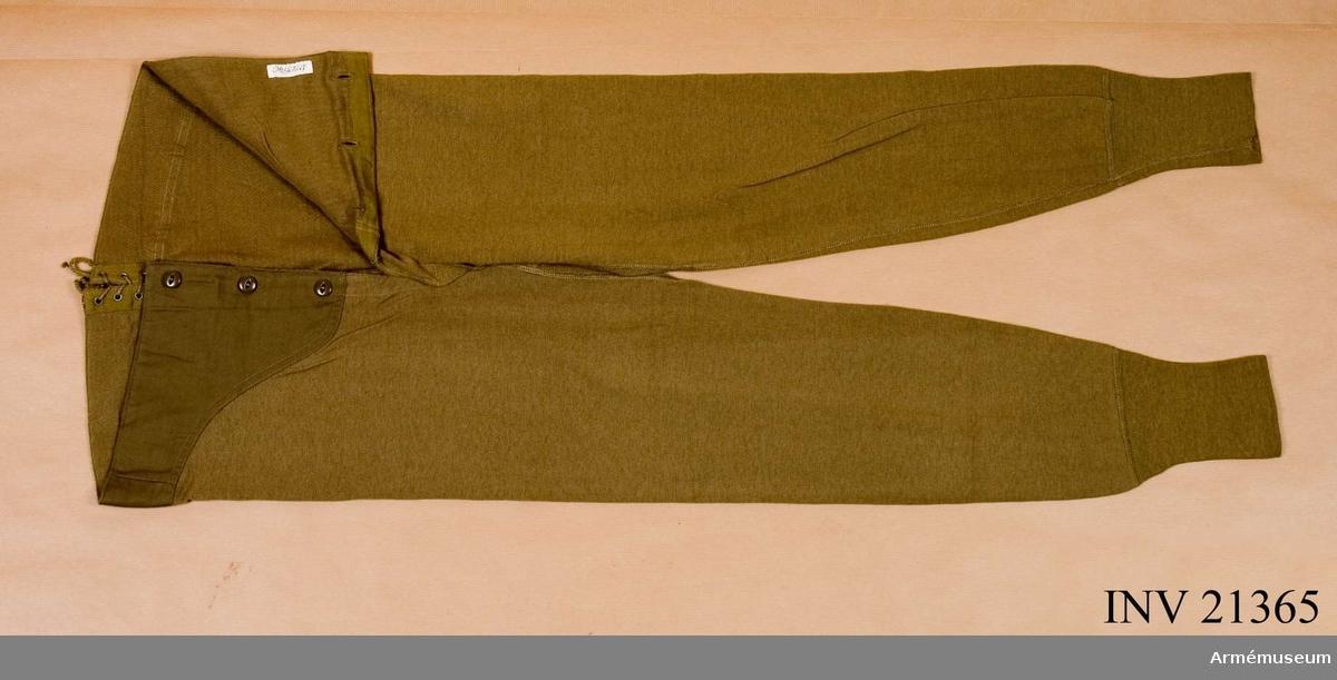 """Grupp C I. Av ylle i kakifärg. På framsidan sprund med 3 kakifärgade ben- knappar. På baksidan - sprund med 3 par järnringar och snören för att sätta fast sprunden. Vid sprundet finns stämpel med påskriften: """"Drawers, wool 50 % Cotton, 30 % Wool wool O.D. Size 32 Stock No - 55- D - 5-28 Stec. P.Q.D. 74 B Chalmers Knitting Co. Cont. W 669 Q.M. 2673 March l.1943 Phila Q.M. Derot""""."""