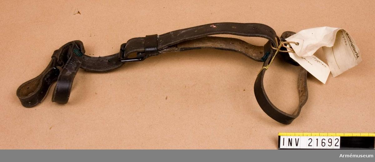 Grupp C II. Kappremmar. Svarta. Består av rem, b:35 mm, med svart järnspänne, som förbindelserem till 2 smala remmar, b:20 mm, med spänne för att binda fast omkring rullad mantel.