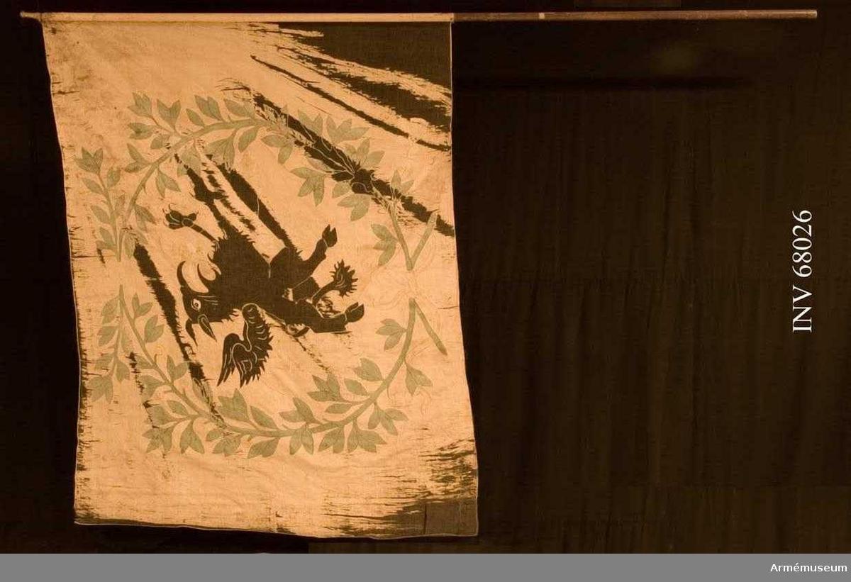Duk: Sydd i två våder. Enkel. Duken kantad med liten rundfåll (litet band inlagt).  Dekor: Omvänt lika dekor på båda sidor. Utförd i sidentaft med broderade konturer, Södermanlands sköldemärke, en svart grip. Röd (mycket blekt) tunga. Gripen omgiven av lagerkrans i grönt, lagerkvistarna nertill med rosett av gult band, endast konturerna broderade, långa tofsprydda ändar. Plattsömsbroderier i gult och blått silke.   Stång: Tillverkad av brunmålad furu. Avsågad.  Holk av förgylld mässing (jämför nr 28199). Spets saknas.
