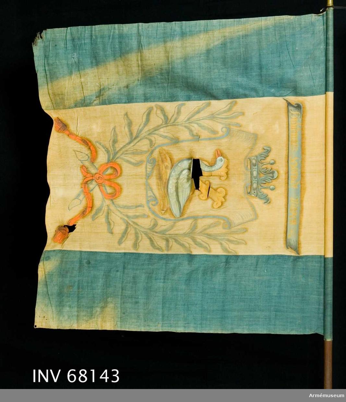 """Duk: Tillverkad av enkel gul och blå linnelärft. Fäst med en rad tännlikor på ett blått band.  Dekor: Målad omvänt lika på båda sidor på det gula fältet. I den med öppen krona krönta skölden är en gås i grått med orangeröd näbb placerad. Skölden innefattad av två kvistar i grå-blått (även ramen runt skölden och kronan), som är sammanbunden nedtill i rosett. Bandet i orangerött med långa tofsprydda ändar.   Över det hela ett språkband i grått med text i gult. I skölden har det förut varit målat ett K, vars utskjutande delar, förutom """"gåsen"""", har övermålats med gult.  Stång: Tillverkad av brunmålat trä. Saknar spets. Holk av förgylld mässing."""