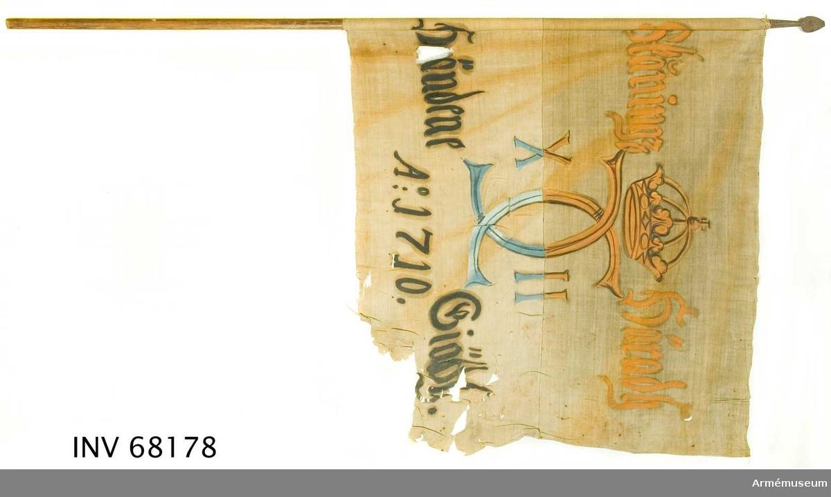 Duk: Tillverkad av enkel vit linnelärft. Två horisontella våder sammankastade (på dukens insida). Vertikala ytterkanten lagd åt dukens insida. Fastsydd runt stången.   Dekor: Målad endast på dukens insida dock är namnchiffret och kronan ifyllda på utsidan, i mitten Carl XII:s namnchiffer, krönt med sluten krona, dubbelt C, på ömse sidor om detta X-II.   På den övre våden i gult och brunsvart, på den nedre i blått och svart.  Text på ömse sidor om chiffret, upptill i gul och nedtill i svart. Under chiffret text i svart.  Stång: Tillverkad av trä, avsågad. Holk försedd med lansettformad spets. Holk och spets av järn.
