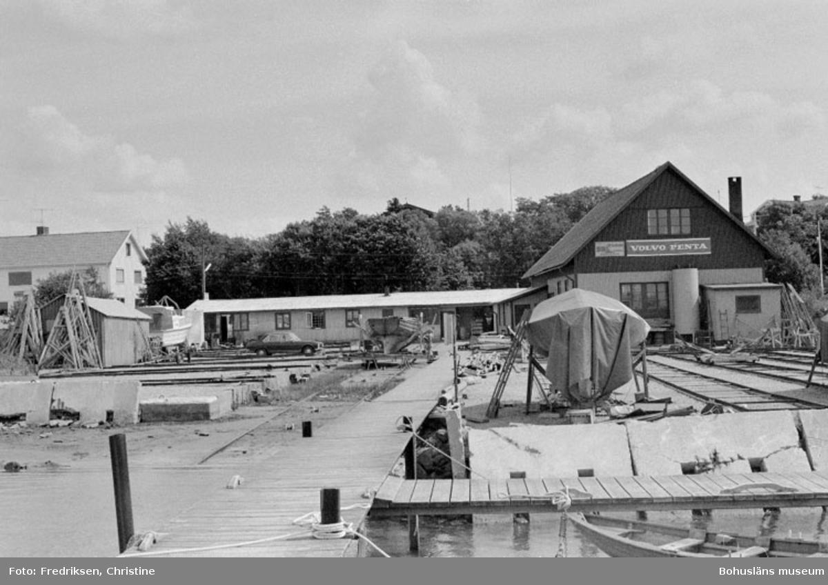 """Motivbeskrivning: """"Stenungsunds Båtvarv, till höger båtbyggarverkstaden, strax vänster därom f.d garage som numera används som försäljningslokal. Bilden tagen från bryggan."""" Datum: 1980-07-15 Riktning: Ö"""