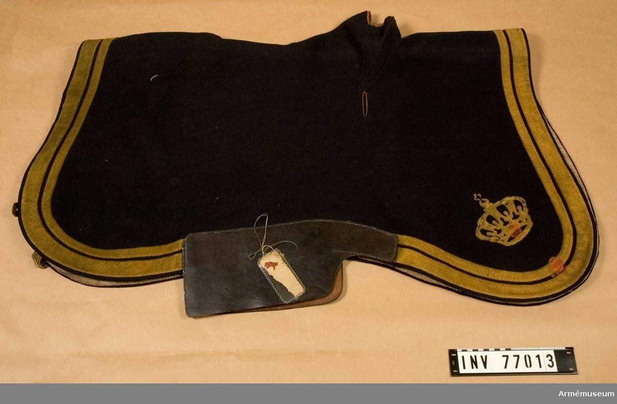 Grupp K I. Regemente K. Skånska dragonregementet. Land S.  Tillverkad av mörkblått ylletyg med två gula lister (den inre smalare). Rundade hörn med kunglig krona av förgylld brons.