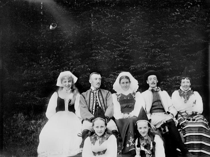 """Enligt fotografens noteringar: """"Grupp vid Tennisplanen."""" Plats: Kasen Datum: 22 Juli 1899 Tid: Kl 5 em. Ljus: Solsken Bländare: No 2 Objektiv: Svenska Express Exponering: Hastighet No. 3 Framkallning: Hydrochinon, Eikonogén"""