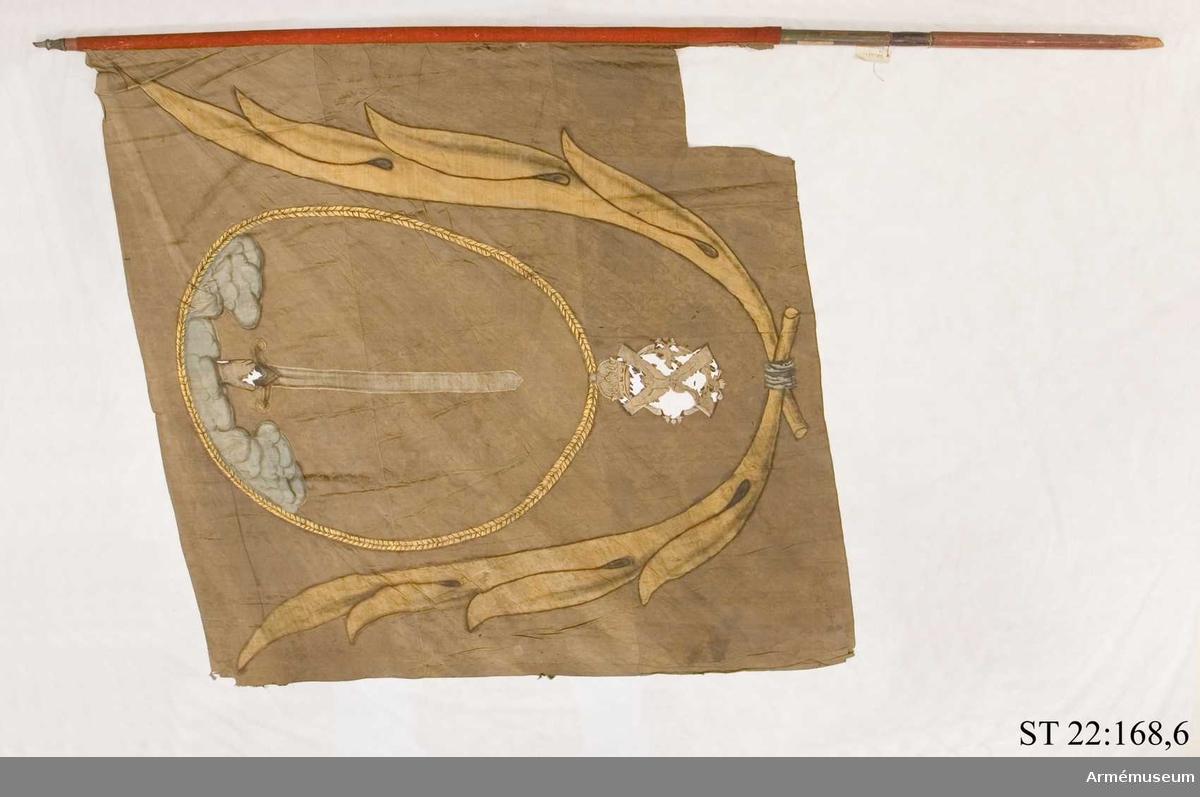 """Duk av brun kinesisk sidendamast. Dekor i intarsia och målade detaljer. Motivet föreställer en hand med svärd som kommer ner ur ett moln omgivet av andreasordens kedja med dess insignier nedtill. Det hela omgivet av nedtill korslagda palmkvistar. Ett kvadratiskt stycke i nedre stångsidan är bortklippt (?) ur duken. Grönmålad, slät stång. Urtaget """"handtag"""", nedanför detta är stången kantig och rödmålad. Stången avkortad. Spetsen avbruten. Endast holken bevarad."""