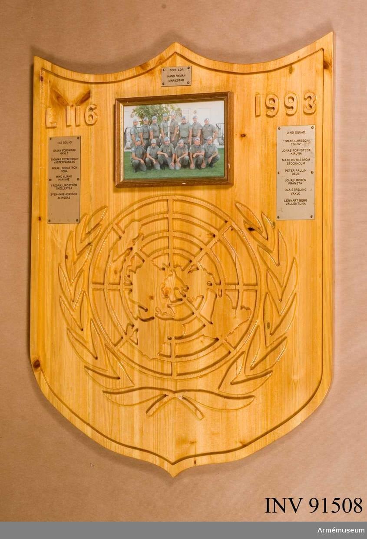 Trätavla med namn på mässingsplattor samt foto på L 116, 1993 (14 man)