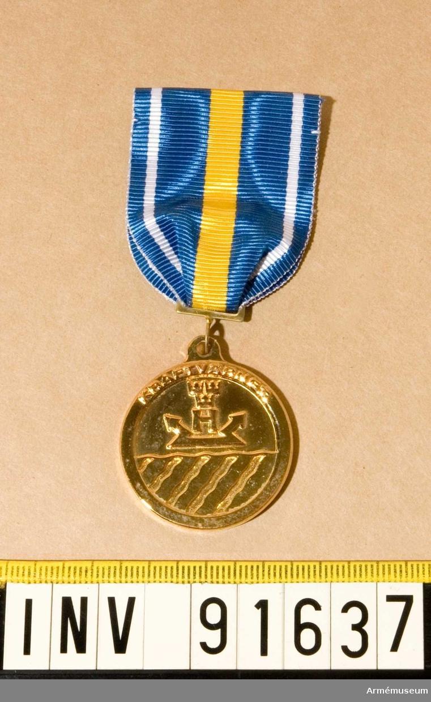 Medalj i guld. KraftvGM.  På framsidan Kraftvärnets vapen och text. På baksidan en krans och text.   Band i blått med vit rand på vardera sidan och en bred gul rand på mitten.