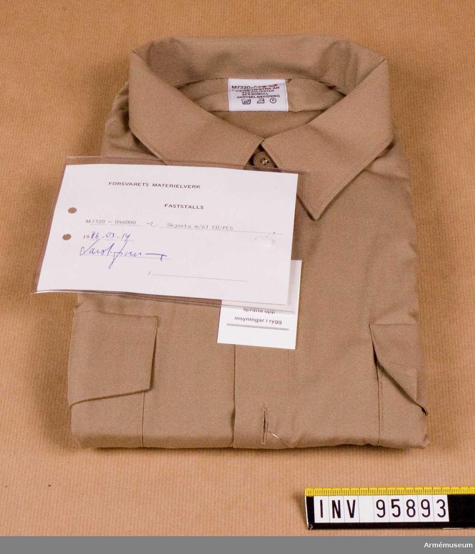 """Skjortan har hel, fast krage och ok av dubbelt tyg och motveck i ryggen samt bröstfickor med lock, som är knäppbara. Skjortan har fasta axelklaffar (42-45 mm) utan hylsor. Skjortan är avsedd för uniform m/61 (tropik) för alla försvarsgrenar. Vidhängande etikett: """"Försvarets materielverk Fastställs M 7320-046000-7, Skjorta m/61 CO/PES, 1986-03-14 (oläslig underskrift)""""."""