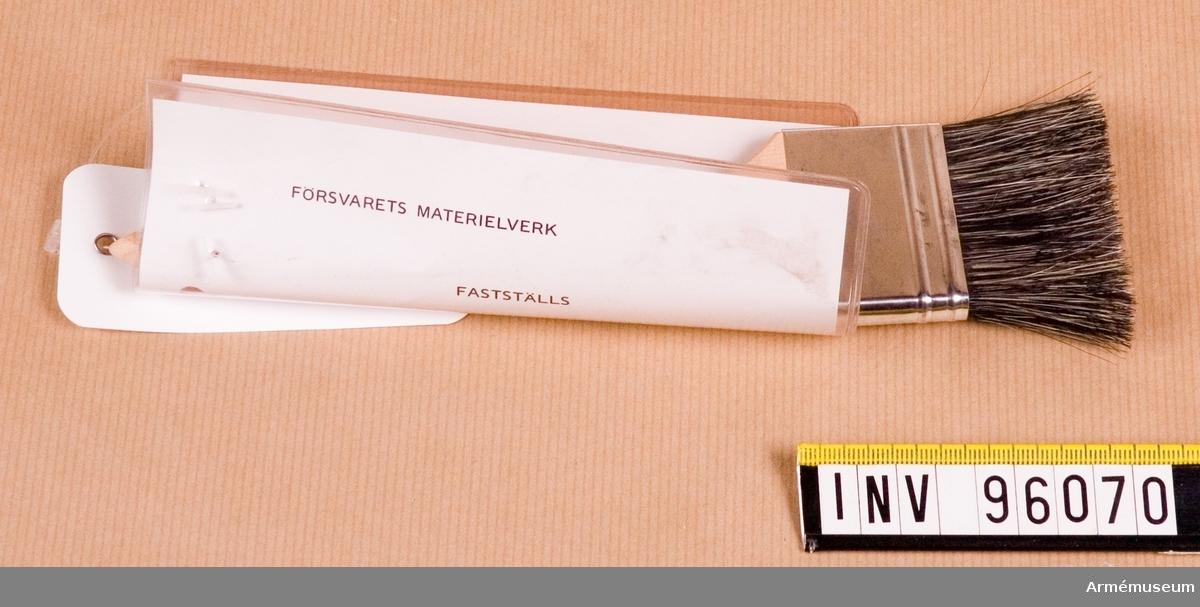 """Vidhängande etikett med text: """"Försvarets materielverk,Fastställs, M6420-872010, Skidvallningspensel, 1985-10-01 (oläslig underskrift)"""""""