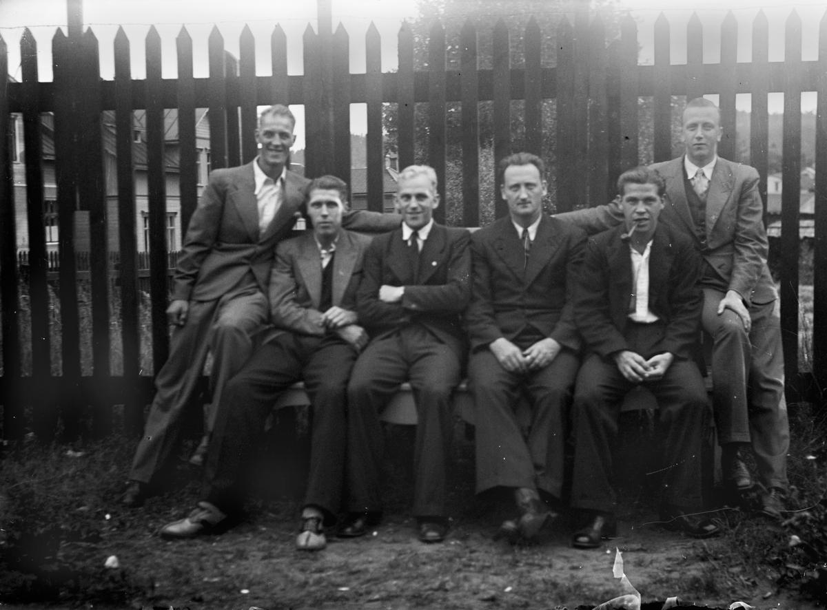 Sex män sitter på en bänk framför ett högt trästaket med byggnader bakom.