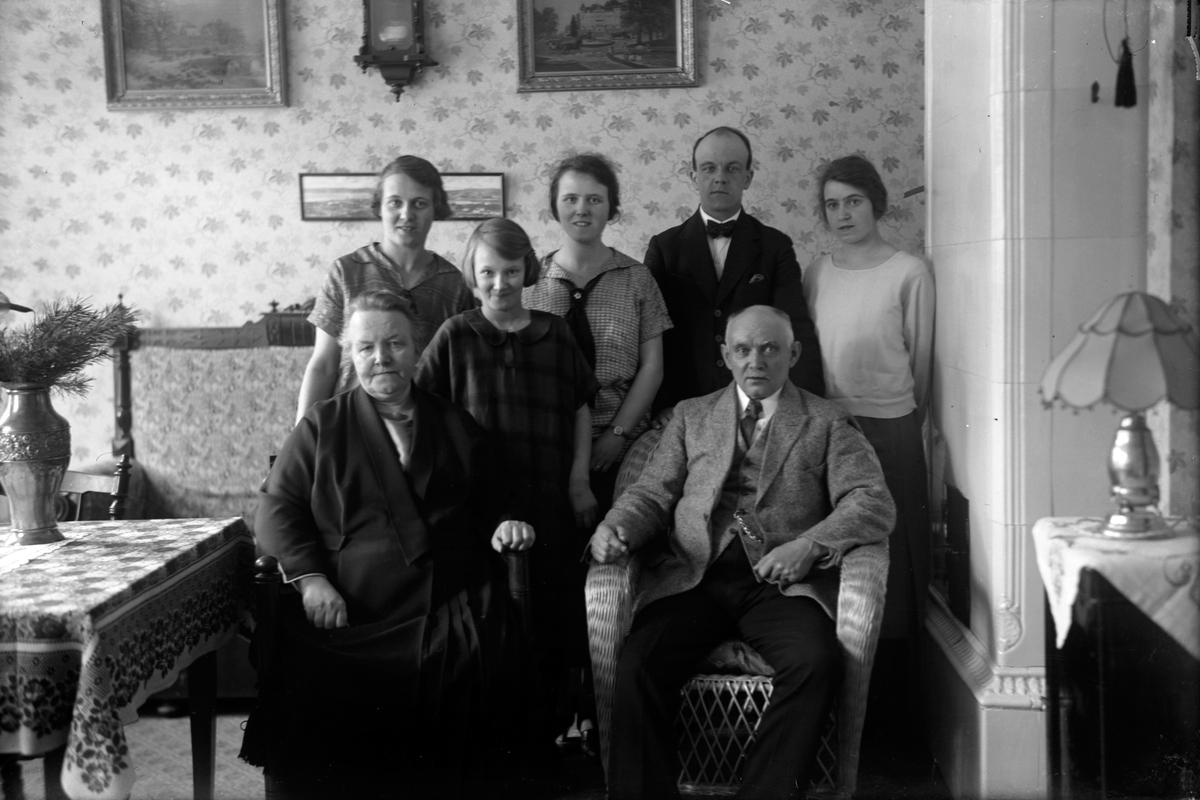 En kvinna och en man sitter i varsin stol. Bakom dem står en yngre man och fyra unga kvinnor.