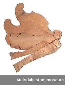 Möbelmall av papp, för detalj till stol. En av sex mallar (med Mölndals stadsmuseums föremålsnummer 00417-00419, 00454, 00591, 00589), ihopsatta med snöre men som förmodligen inte hör ihop.Litteratur: Red. Särnstedt, Bo: Lindome Västsvenskt möbelsnickeri under 300 år, Stockholm 1977. Utställningskatalog från Liljevalchs Konsthall 1977-06-30 - 1977-09-11. Se sid. 22-23 för historik kring fam. Thorsson.Mölndals Museum: Lindomemöbler, Länstryckeriet Göteborg 1994. Utställningskatalog innehållande kapitel rörande familjen Thorssons verksamhet.