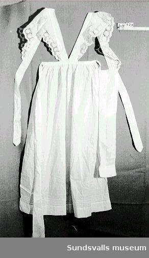 Serveringsförkläde med knytband i midjan och axelband med spetsbrodyr.