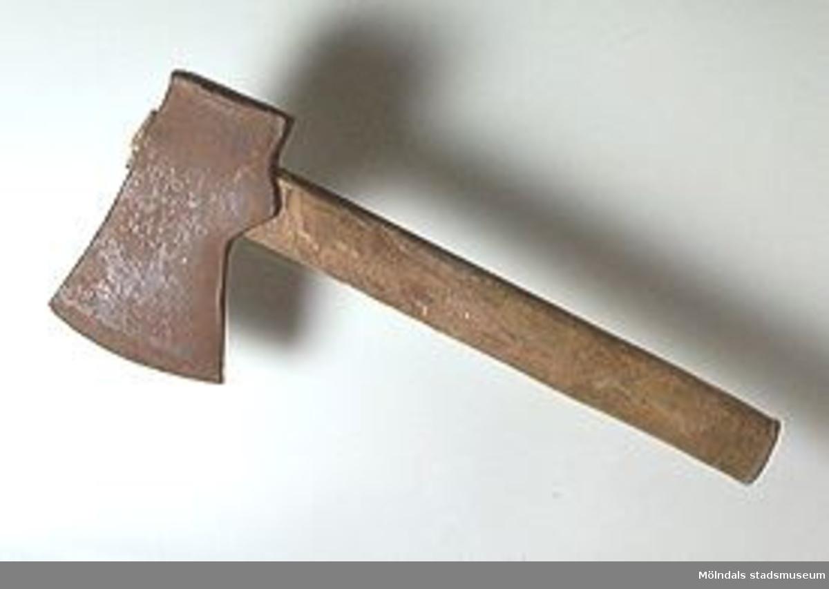 Yxa med träskaft med spår efter bankningar för att yxhuvudet skall sätta sig bättre. Yxhammaren har ofta och flitigt använts som hammare. Troligen från Hisingen.Järndelen bär stämpeln: SATER (?) MATER.Längden ovan inkluderar skaftet.