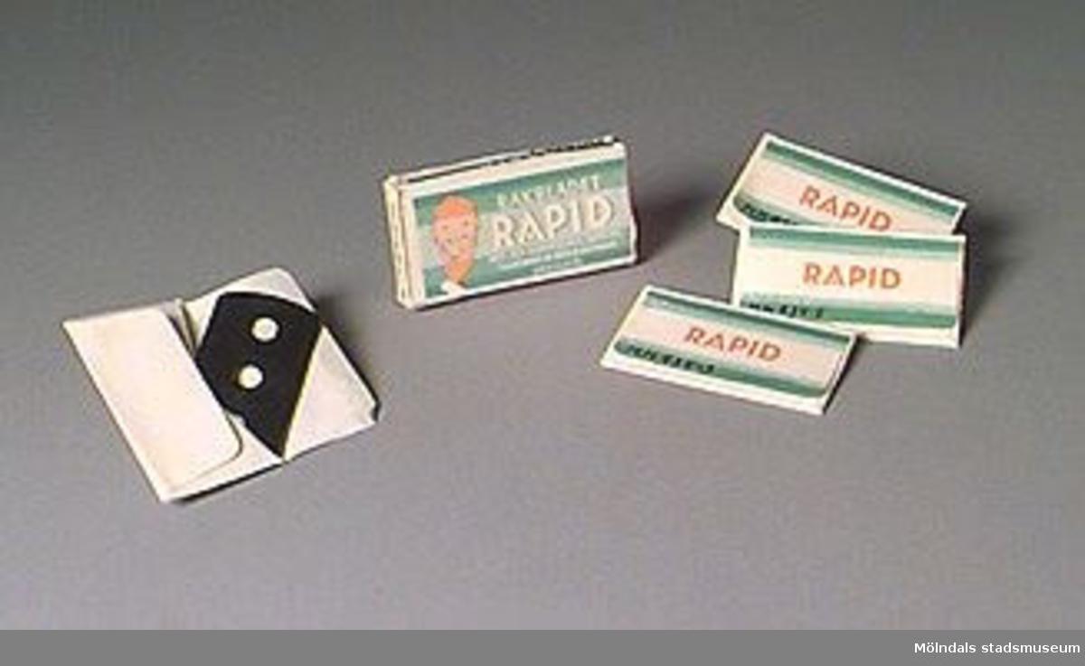 """Grön-vit-orange pappersförpackning med fem rakblad inslagna i papper. Text på förpackningen: """"Rakbladet RAPID med den garanterade skärpan. Tillverkat av bästa svenska specialstål"""". Bild av mansansikte. Varje omslag har samma motiv och text som förpackningen.Inköpt på Anders Antik i Örkelljunga."""