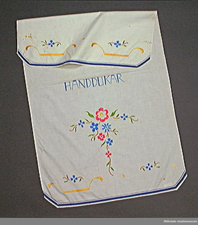 """Vit, kantad med blått band. Broderat: stiliserade blomkorgar i gult med blå blommor samt """"Handdukar"""". Blomranka i rosa, blått och grönt.Broderierna delvis borta."""
