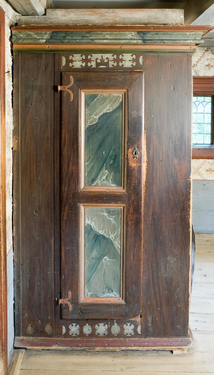Skåpsäng av trä, platsbyggd. Bred profilerad rak krönlist. Fotänden med skåp, dörr med två speglar, profilerade. Gångjärn, nyckel, nyckelbricka och lås i smide. Dessutom en smal dörr på sängens långsida, nästan gömd bakom två speglar. Smidda gångjärn och lås men ingen nyckel,  enbart hål för nyckeln. Reliefmönster ovan och under dörrarna, dessutom som mittparti på smala dörren. Långsidan med svängda hörnskivor, därunder profilerade lister upptill och nertill på sidostycket. Målad i rödbrunt, med delar av profileringen i gulockra och ådringsmålning, speglarna med ådringsmålning i blått, grått, vitt. Reliefen förstärkt med vit färg mot det rödbruna.