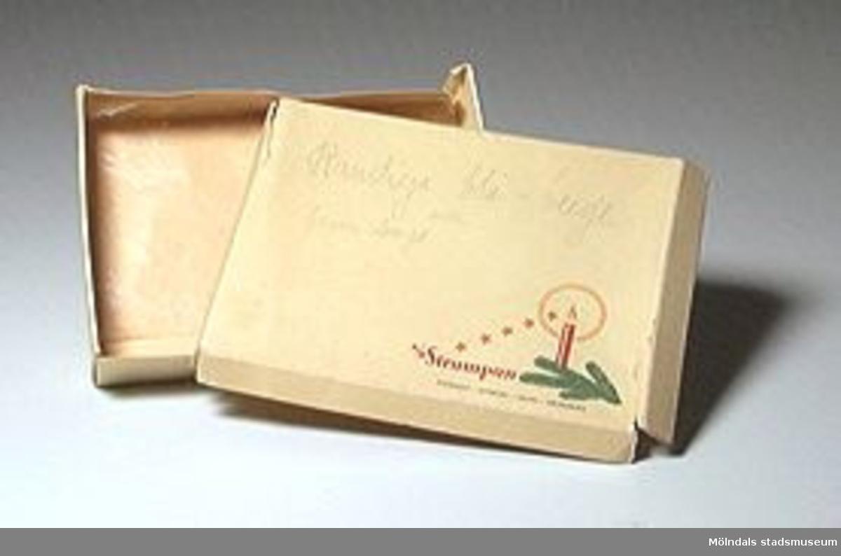 Mindre kartong som en gång innehållit nya strumpor. Detaljistförpackning. På locket finns en bild av ett rött stearinljus på en grankvist, samt texten; A/B Strumpan Stockholm - Göteborg - Malmö - Helsingborg.