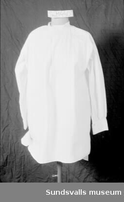 Vit skjorta med rund hals och sprund. Bröstficka. Små silverfärgade knappar på manschetterna.