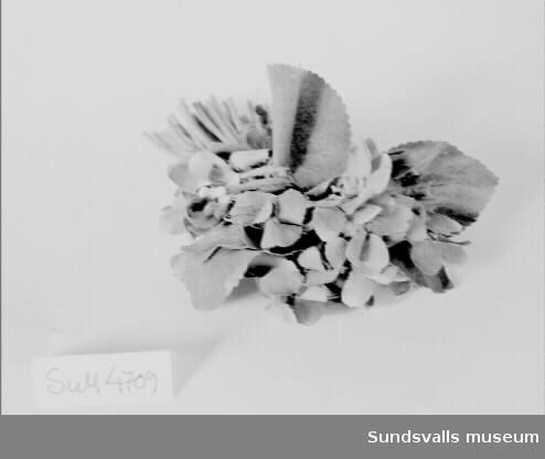 Tygblomma i form av en bukett med violliknande tygblommor i mörkt lila med blad i grönt tyg. Gröna tygstjälkar som knutits ihop med bast. Dekoration till klädedräkt.