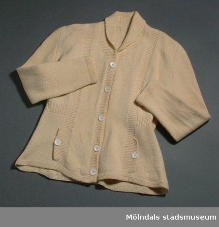 Benvit stickad ullkofta med stora vita knappar som knäppning på framsidan. Har fickor på båda sidorna om knäppningen.