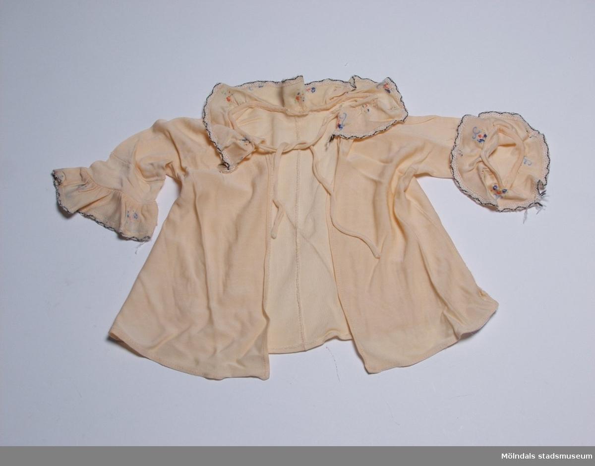 Spädbarnsskjorta i laxfärgad charmeuse. Halsringning och ärmar har blommönstrat rysch i samma kvalitet.