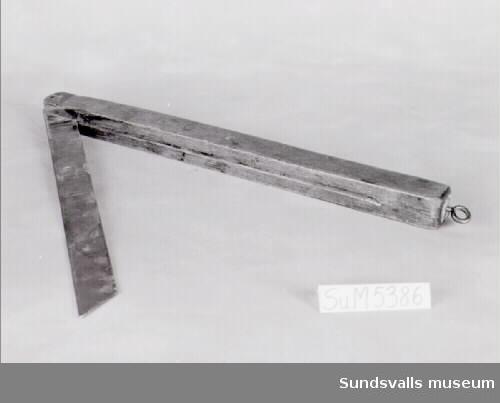 Smygvinkel bestående av ett stålblad och en trädel. Bladet kan fällas in i en skåra i trädelen. I ena änden sitter en metallögla fastskruvad som upphängningsanordning.