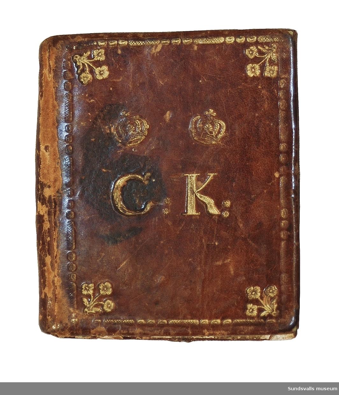 Nålbrev med pärm i brunt läder med präglat och förgyllt blomster- och kronmönster. På ena sidan finns initialerna CK och på andra sidan årtalet 1786. Invändigt är ett stycke grön textil fastsytt och pärmarna är fodrade med papper. Följande upplysningar är handtextat på en lapp som klistrats fast på insidan av pärmen: 'Catharina Kroon, f. 14.2.64 (1764) d. 5.3.1817, gift med rådman Jonas Thunberg i Sundsvall'.