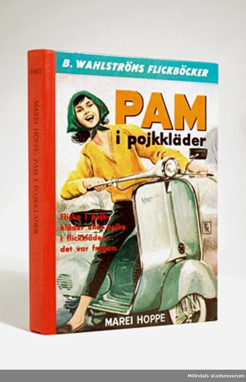 Bok: Pam i pojkkläder av Marei Hoppe, B. Wahlströms flickböcker. På framsidan är det en flicka som kör vespa. På baksidan listor över boktitlar. Röd tygrygg med nr 1067. Pris 3:70.Givaren fick denna bok av sin faster Maj, julafton 1961. Hon önskade sig alltid böcker vid jul och födelsedag och fick många av sin faster.Hennes barn läste boken under 1980-90-talen.