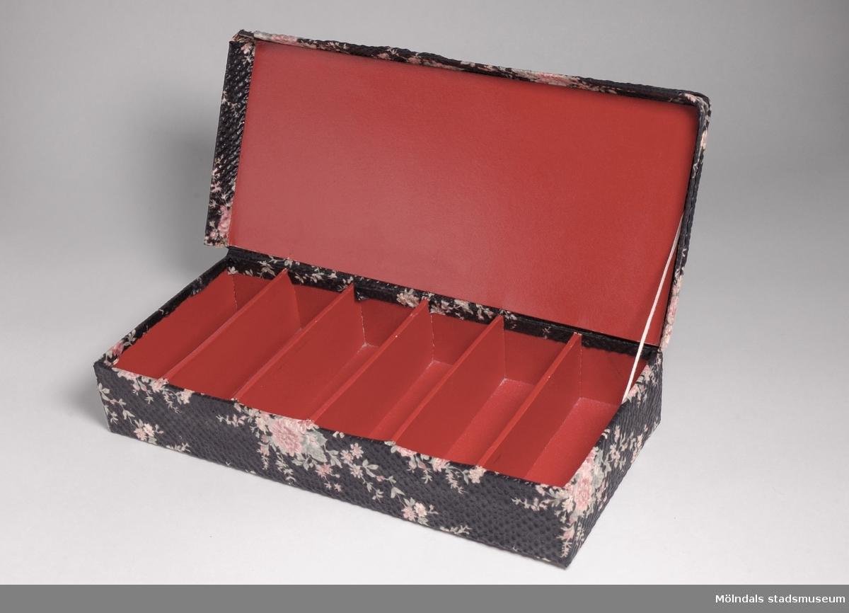 Asken är gjord av röd pappkartong. Klädd i blommönstrat crepe nylontyg. Tyget är påklistrat. Ser hemmagjord ut.Ägarinnan Rut Larsson arbetade 10 år på Papyrus mellan 1934-1944.