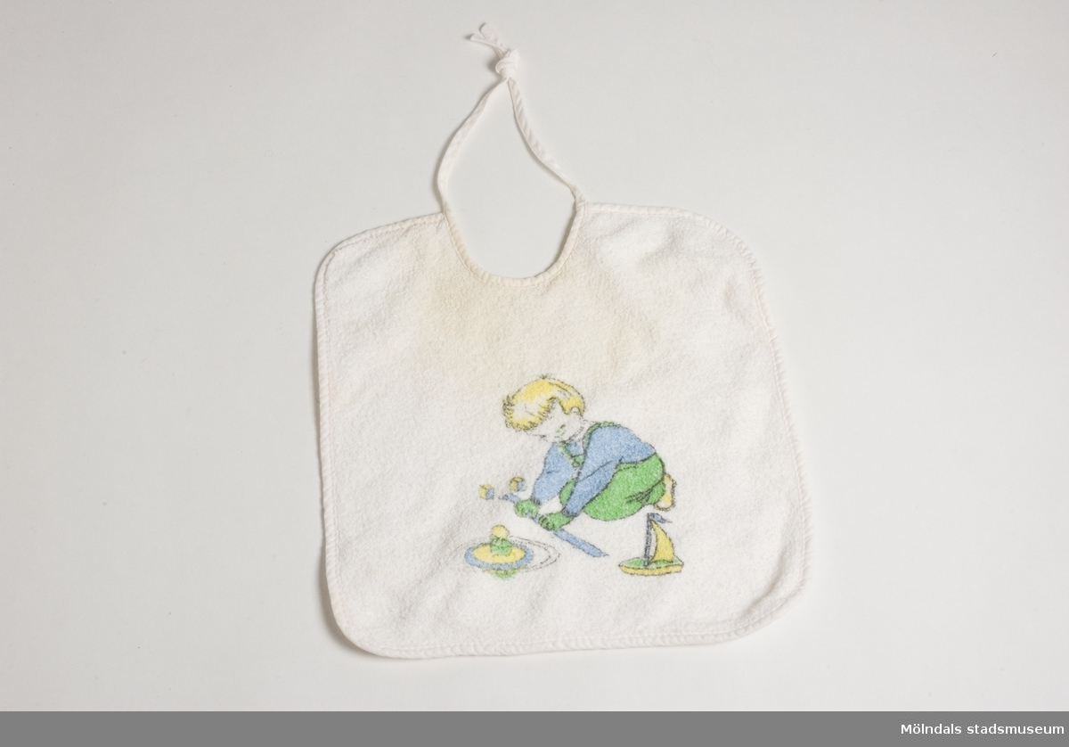 Haklapp av frotté. Vit färg med tryckt dekorbild av lekande pojke. Fästes med snören i nacken. Har troligen brukats av Kerstin Olofsson till barn på 1970-talet.