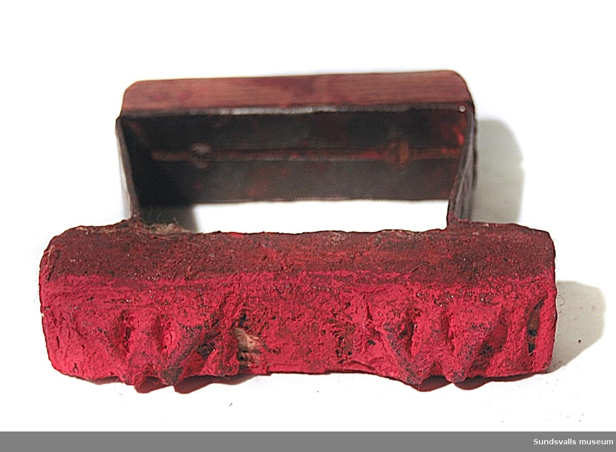 Seppningsmärke av trä med två gummiplattor, indränkta i röd färg, märkta 'W'.