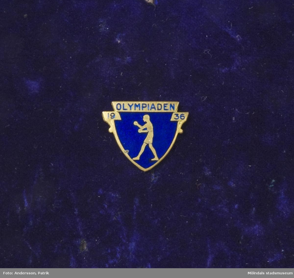 Idrottsmärke ägd av tungviktsboxare Henry Nicklasson, till minne av Olympiaden 1936.Sköldformat märke av metall med blå emalj, samt texten OLYMPIADEN 1936, samt stiliserad boxare. Nål för fastsättning på baksidan.