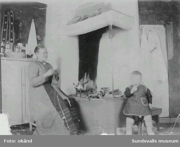 Köksinteriör. Kvinna med stickning och barn på en pall, sittter vid  öppen spis. Kopparkaffepanna på trefot. Okänt ursprung.