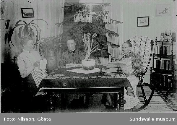 """Tre kvinnor som sitter vid ett bord med böcker. Anteckning """"Fr. Söderberg"""""""