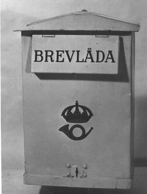 Brevlåda med sluttande tak mot front och gavlar. På frontenett brevinkast med klaff, försedd med text:se MRK. Mitt på brevlådanett postemblem av 1912 års emblem. Brevlådan tömmes från botten.