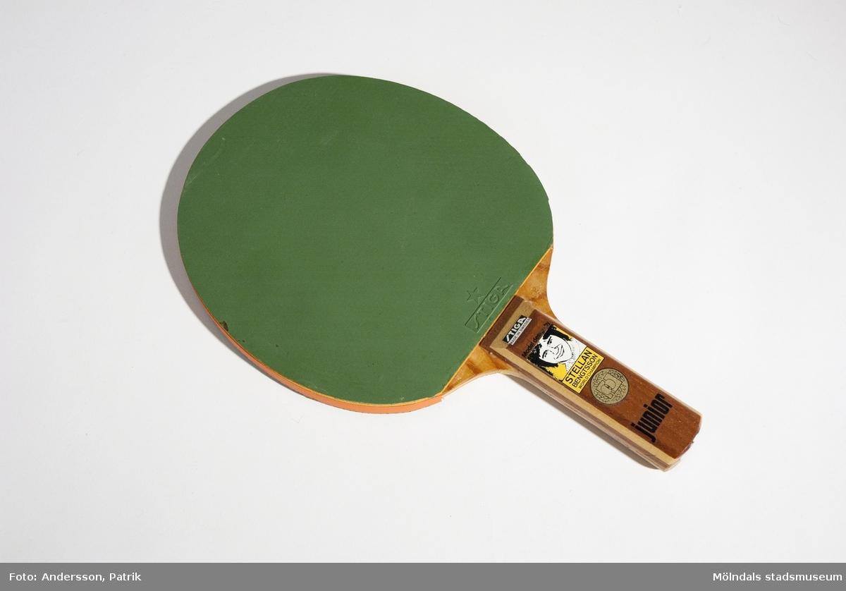 """Oandvänt junior bordtennisrack från 1970-talet, märke """"STELLAN BENGTSSON WORLD CHAMPION""""1971 blev Stellan Bengtsson den första svensk att vinna VM-guld i singel bordtennis. Därför fick han vara med vid produkutveckling av tävlings - och motionsutrustning och gav därmed STIGAs bordtennisprodukter ett världsrykte.  Racket är gjort av en trästomme och har pålimmande gröna gummibeslag på båda sidor.På skaftet sitter det klistermärken med texten: """"STIGA MADE IN SWEDEN"""", """"Model design by STELLAN BENGTSSON WORLD CHAMPION"""" och """"junior"""".MåttDiam: 153 mm, Höjd: 9 mm, Längd med skaft: 257 mm, Längd på skaft: 95 mm, Bredd på skaft: 28 mm, Höjd på skaft: 23 mm."""