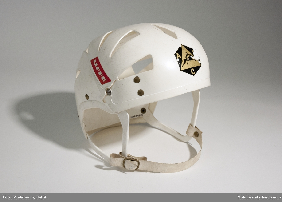 """Ishockeyhjälm i juniormodell från 1970-talet.Hjälmen är vit och har band under hakan. Den har några repor i plasten.På vänster sida av hjälmen sitter klistermärket """"UFFE"""" i rött och vitt. I pannan sitter ett klistermärke med ABC-Fabrikernas logotyp som består av bokstäverna A B C och en häst med ryttare. Logotypen går i färgerna guld och svart. Märket är något slitet. I nacken sitter också ett slitet märke, där motivet är okänt.På vänster sida av nacken finns """"ABC-FABRIKERNA KUNGÄLV SWEDEN"""" tryckt i plasten.Hjälmen användes av givaren när han var liten och bodde i Balltorp.Gåva av Anders Forsberg, Åkersberga."""