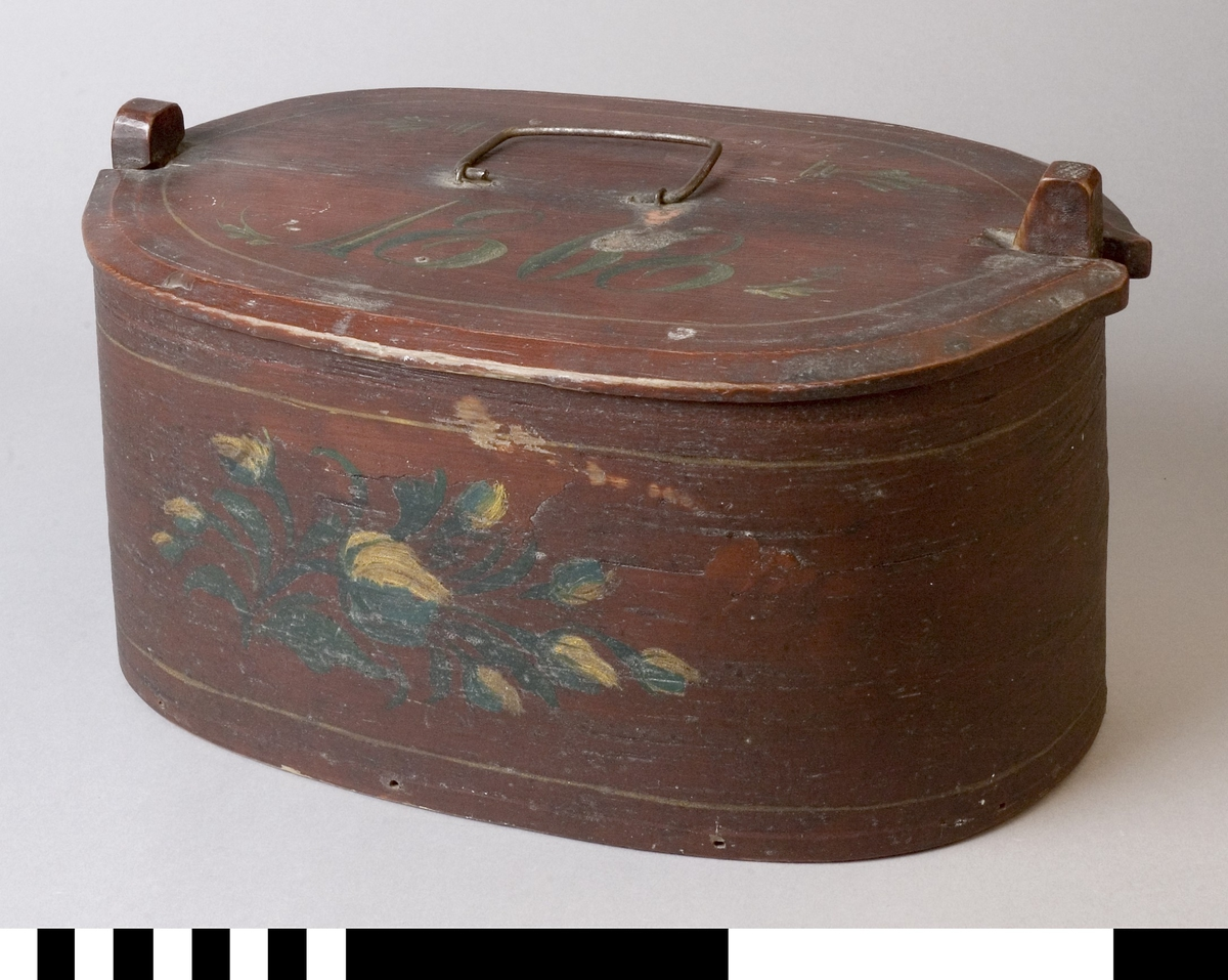 Ask tillverkad av trä. Oval form med knäpplock och med handtag av järn. Framsidan dekorerad  med blomstermotiv.