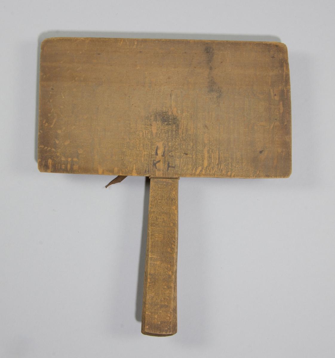 Karda bestående av en rektangulär platta med ett längre, smalt skaft, bokträ. Plattans insida täckt med piggar av ståltråd, trädda genom ett stycke skinn.
