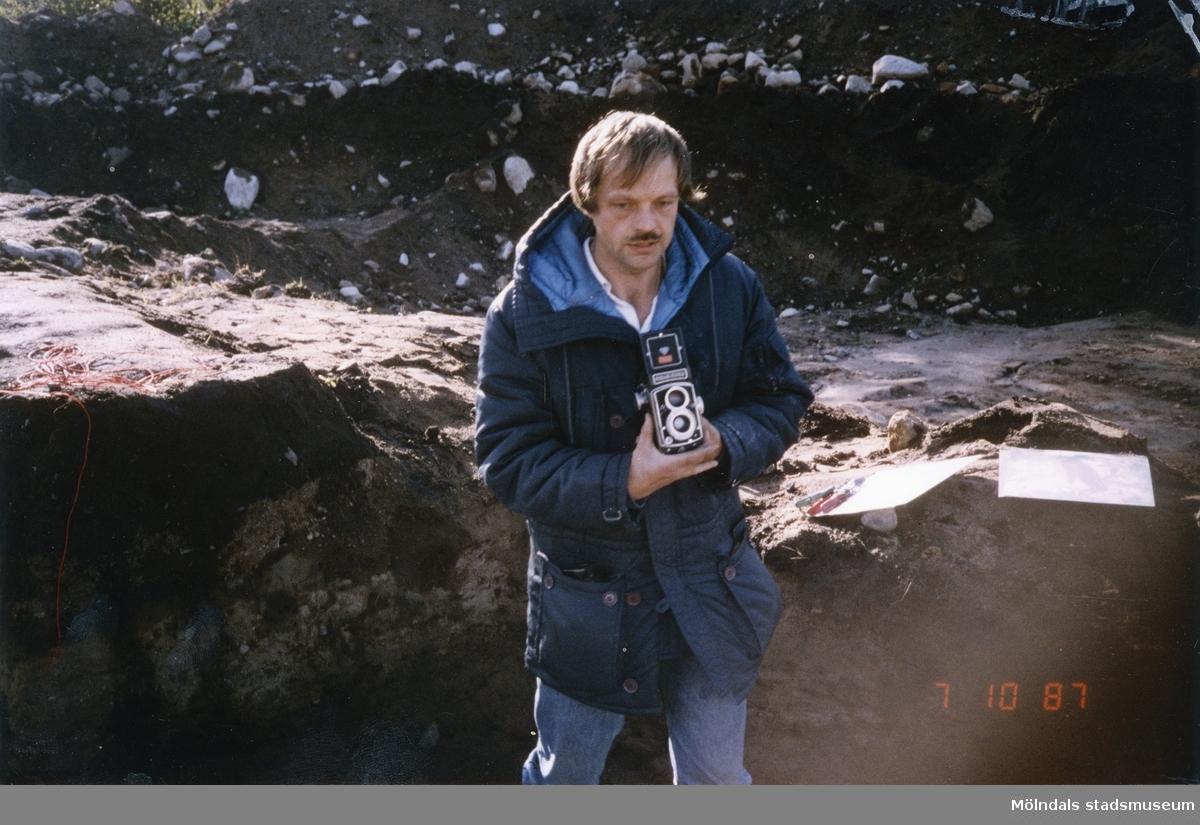 Bengt Nordqvist vid en utgrävning med en kamera i handen. Bilden är troligtvis tagen i Balltorp 1987.