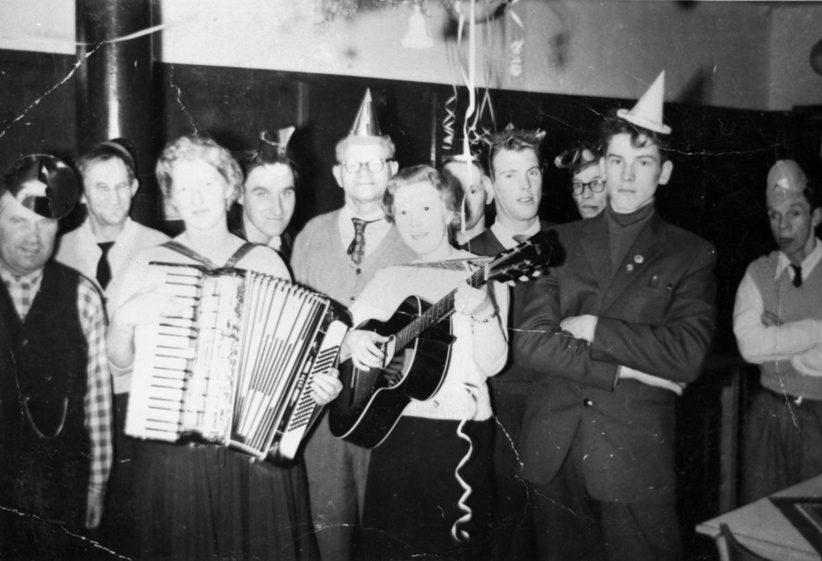 Festklädda elever och personal i manliga arbetshemmet på Stretereds skolhem, nyårsafton 1959. I förgrunden kvinnor med dragspel och gitarr. Med på bild fr.v. Åke Magnusson.