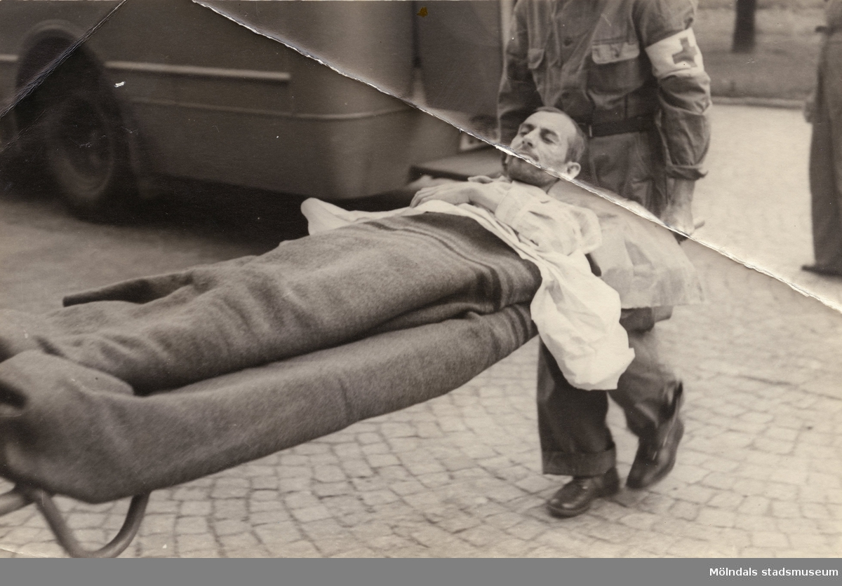 """""""Karantänsförläggning"""" på Kvarnbyskolan för flyktingar från koncentrationsläger i Tyskland 1945. Manlig flykting på bår, buren av Röda Korsets personal."""