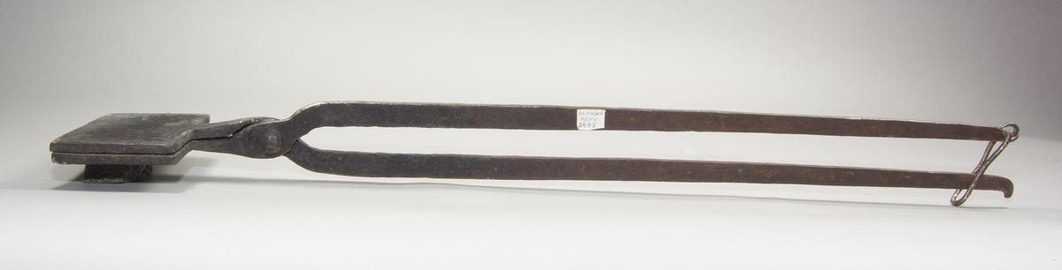 Rånjärn eller gorånjärn av järn. Mönstrade rektangulära plattor som är gängade med varandra. Två stänger med handtag längst ut på skaftet.