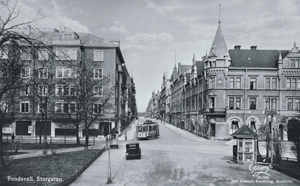 """Storgatan från söder med  """"Casselska huset"""" till höger. Skylt på fasaden """"Grand Cafe"""". På bilden spårvagn samt bil. På vykortet bildtexten """"Sundsvall Storgatan, Fotograf Axel Eliasson, Konstförlag Stockholm""""."""