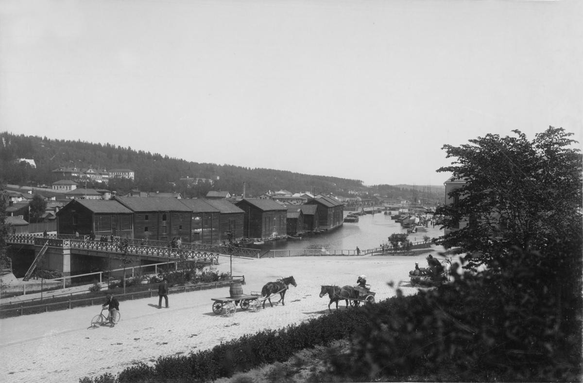 Vy med magasinen på Norrmalm, närmast Storbron, i bakgrunden Medelpads lasarett och till höger västra Storgatan med trafikanter. Vykort.
