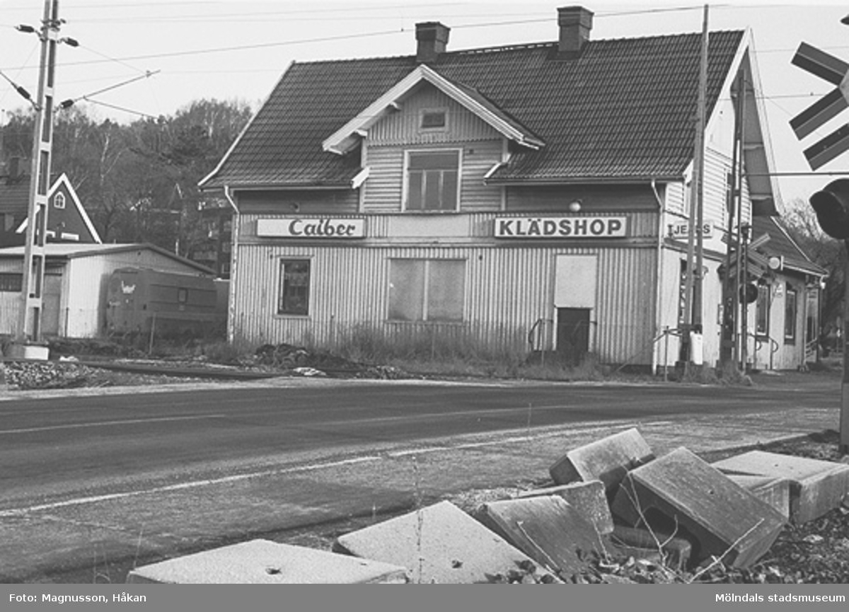 """Byggnadsdokumentation inför rivning. Kållereds stationshus på Gamla riksvägen i Kållered centrum. När fotot togs så låg den mycket populära jeansaffären """"Caiber klädshop"""" i byggnaden. Ungdomar """"vallfärdade"""" dit pga butikens moderna jeans  med lägre priser. I bakgrunden, längst till vänster, ligger Kållereds värdshus (senare vårdcentral). Järnvägen går precis utmed fastigheten. Foto: Håkan Magnusson, Kållered, 1991."""