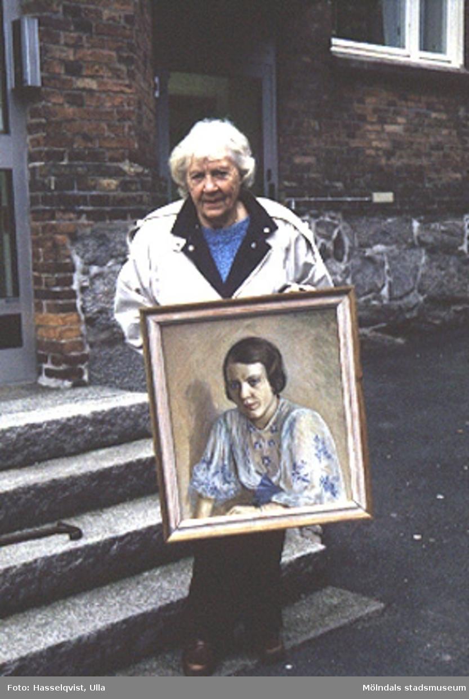 Målning utförd av Teodor Lindbäck, Lindome, 1934. Olja på duk. Porträtt av Margit Hult, f, Johansson 1910. Margit flyttade till Bräckavägen i Lindome 1934 och sökte upp Lindbäck, då hon själv var intresserad av konst. De målade tillsammmans. Margit äger tavlan och håller upp den på fotot.