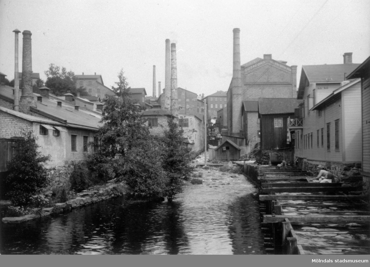 Kvinnor sköljer tvätt i kvarnbyrännan, 1920. I bakgrunden Götafors fabrikers gavel.