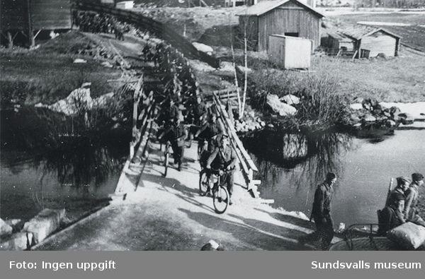 """""""Et kompani kommer til leiren etter utmarsj."""" (Einar Lian, Trondheim, februari 1989)""""Dette er den gamle bana over elva like för bakken opp mot leiren på Baggböle. I dag er der jo bygget ny bru. Det er en sanitetstropp som befinner seg på brua. Vi benyttet mye sykler i tjensten."""" (Magnus Hovd, Mosby, augusti 1988.)Denna bro måste passeras för att nå skjutbanan, stora vägen till Njurunda, Baggböle by m fl ställen. Bilden är tagen från vaktkuren."""